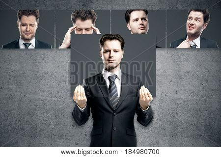 Young european man hiding himslef behind poster with straight face. Row of faces with different expressions in the background. Emotion concept