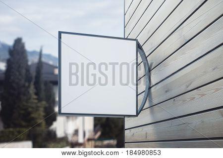 Empty square poster on wooden building. Landscape background. Pub/bar/cafe/shop concept. Close up Mock up 3D Rendering