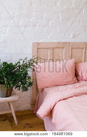 Empty bed with pink pillows and pink cover in the bedroom. White wall wooden floor home flowers with green leaves and small table near the bed. Home interior