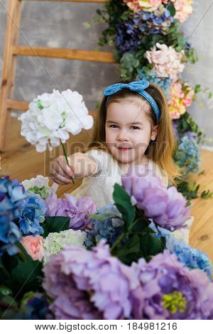 Cute smiling little girl in white lacy dress gives a white flower. Blue bow on her head wwoden stairs decorated with flowers on the background
