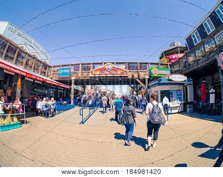 San Francisco, CA, USA - April 3, 2017: Tourists walking near the entrance of Pier 39, Fisherman's Wharf, bridge with Bubba Gump Shrimp Co. sign above