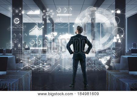 Back view of young businessman looking at abstract business panel in interior. Future concept. 3D Rendering