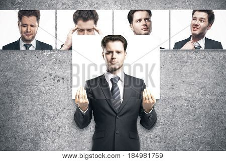 Young european businessman hiding himslef behind poster with straight face. Row of faces with different expressions in the background. Emotion concept