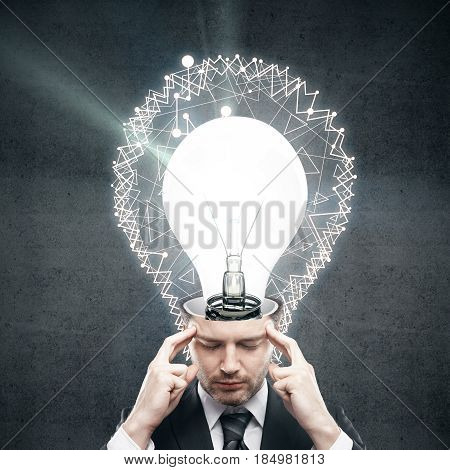Thoughtful young businessman with abstract polygonal lightbulb on concrete background. Idea concept