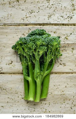 high-angle shot of some stems of broccolini on an off-white rustic wooden table