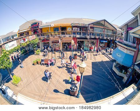 San Francisco, CA, USA - April 3, 2017: Groups of tourists, mainly families, walking at the Pier 39, Fisherman's Wharf