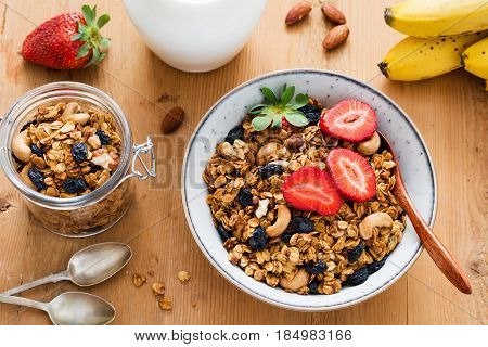 Granola, milk and fruits. Tasty and healthy breakfast: bowl of granola with fresh strawberries, jug of milk, almonds, bananas and spoons on wooden table. Top view