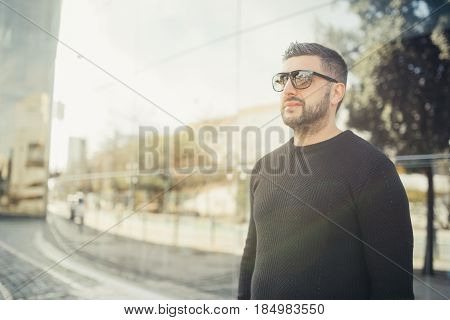 Stylish young business man standing in front his office building.Handsome successful entrepreneur in sunglasses going on a coffee break.Going on lunch on a sunny day out of the office.Casual friday