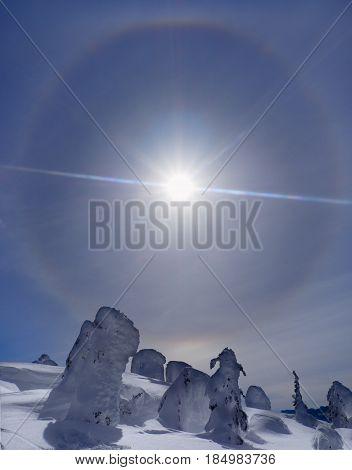 Sun Halo Rainbow in Snow Covered Landscape, Against Blue Sky
