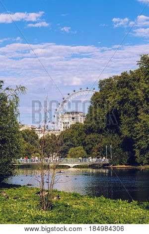 LONDON UNITED KINGDOM - August 21 2015: View over Buckingham Palace the London Eye and the Blue Bridge from St James Park lake