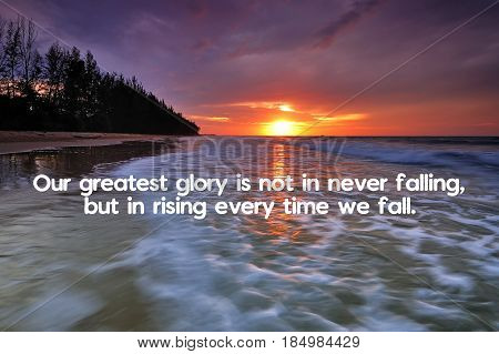 Our greatest glory is not in never falling but but in rising every time we fall - Inspirational quote on blurred background