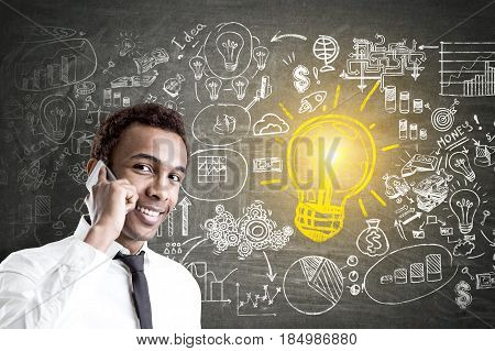 Portrait of a young smiling African American businessman with a smartphone standing near a blackboard with a yellow light bulb and a business sketch on it.