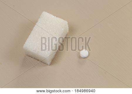 One sweetener tablet near one sugar cube