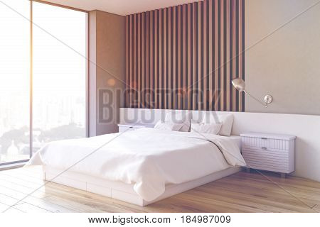 Side view of an interior of a bedroom with gray and light wooden wall element a double bed and two bedside tables. 3d rendering toned image.