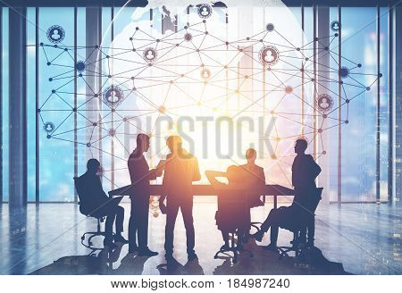 Silhouettes of business people near a table in a conference room. World map and network sketch above them. Toned image double exposure.