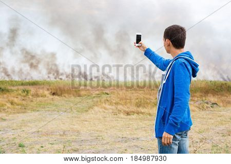 the eyewitness shoots the fire and a smoke screening in fields with grain crops with the phone camera.