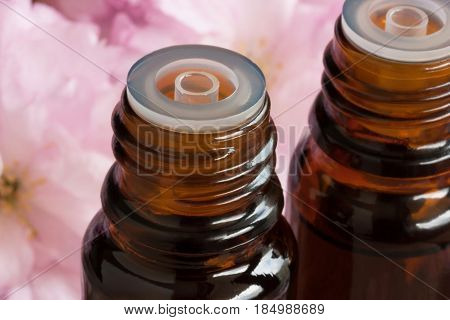 Two bottles of essential oil with pink blossoms in the background
