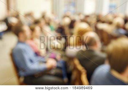 Blurred spectators sit on chairs in rows in the theater and watch the performance