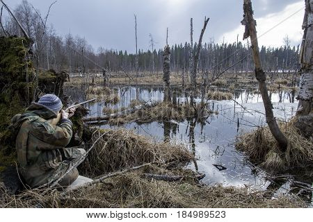 Hunter sitting in the swamp in the forest and aiming at the fowl holding in his hand an old hunting rifle