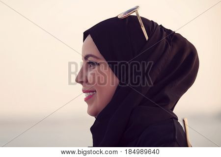 Arab woman wearing hijab smiling enjoying evening time