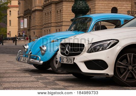PRAGUE, CZECH REPUBLIC - APRIL 21, 2017: A small blue vintage Volkswagen Beetle car next to a big white Mercedes parked in front of the Rudolfinum concert hall