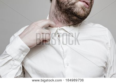 The unshaven man in the white shirt is tight and stuffy and he tries to expand the collar to make a breath