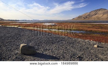 Northern arctic landscape. Coast of the ocean and mountains in the background are visible houses and ships. Surroundings of Longyearbyen Svalbard archipelago (Svalbard island) Norway