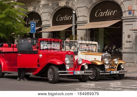 PRAGUE CZECH REPUBLIC - APRIL 21 2017: Two vintage Ford cars parked in front of a Cartier shop in the Parizska street offering sightseeing tours for tourists