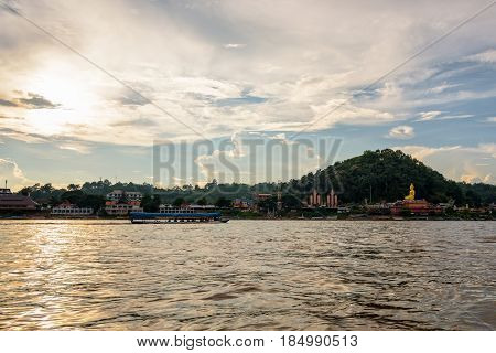 Beautiful natural landscape and tourist boat cruising the beauty of the Mekong River coast at sunset in the Golden Triangle Park (Sob Ruak) in Chiang Rai Province Thailand