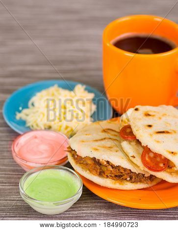 Closeup of a traditional delicious arepas, shredded chicken avocado and cheddar cheese and shredded beef with grated cheese, avocado and pink sauce in bowl on wooden background.