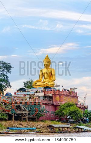Beautiful golden buddha statue of Phra Buddha Nawa Lan Tue on the banks of the Mekong River at Golden Triangle Park (Sob Ruak) during the evening in Chiang Rai Province Thailand