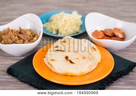 Close up of a traditional delicious arepas, shredded chicken avocado and cheddar cheese and shredded beef on wooden background.