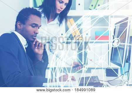 Side view of a serious African American businessman sitting at his desk in office. His colleague is standing beside him. Blue network hologram. Toned image double exposure