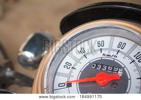 Speedometer on motorcycle dashboard. Round speedometer with red arrow. Speed zero shown. Full stop of motorbike. Transport closeup photo. Motorbike electric gear. Concept image for stagnation