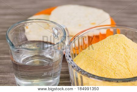 closeup of an arepas flour inside of a cristal bowl, glas of water on wooden blcakground.