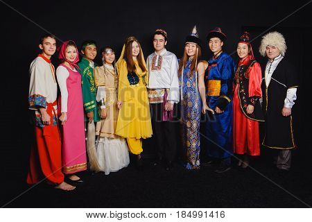 TOMSK RUSSIA - June 21 2016: Students of the Russian nationality of the CIS of the Commonwealth of Independent States in folk costumes against a dark background.
