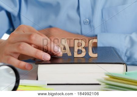 Boy writes in a school notebook wooden letters ABC on the book. Back to school concept