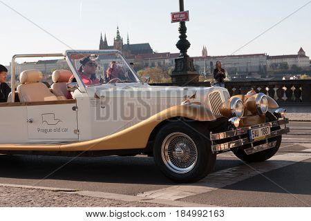 PRAGUE CZECH REPUBLIC - APRIL 24 2017: Vintage car taking tourists for a tour in the streets of Prague with Prague Castle in the background