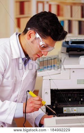 Handsome man fixing a photocopier during maintenance using a screwdriver wearing work glasses.