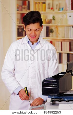 Handsome man fixing a photocopier during maintenance using a screwdriver.