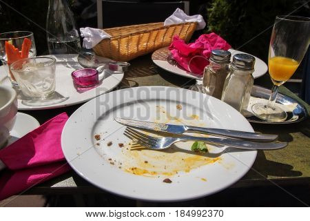 After the outside meal table set with an empty eaten food plate cutlery pink napkins empty bread basket and various dishes selected focus narrow depth of field