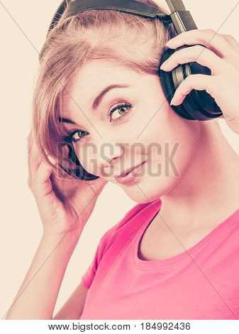 Woman in red shirt big headphones listening music mp3. Smiling female model. People leisure happiness concept.