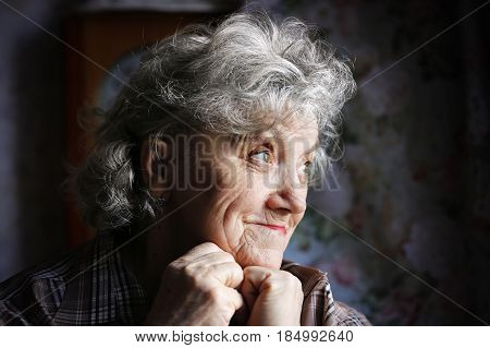Thoughtful elderly woman on a dark background
