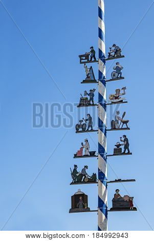 Typical Bavarian maibaum or maypole in blue and white colors with wooden figures of various professions on a sunny day against the clear blue sky with copy space in Dorfen Bavaria Germany vertical
