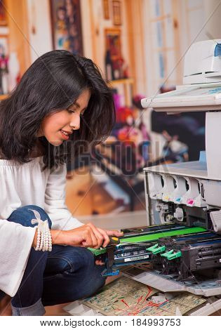 Beautiful woman wearing a white blouse, crouching and fixing a photocopier and smiling during maintenance using a screwdriver.