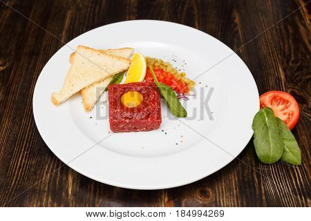 Delicious classic steak tartar with beef pepper onion and slices of bread close-up