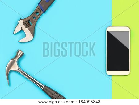 Smartphone repair background template with a lot of free blank copy space for text and content for cellphone fixing company's offer or sale ad. Mobile phone and tools on light green and blue table.