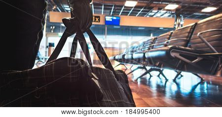 Terrorist in airport planning a bomb attack. Terrorism and security threat concept. Suspicious dangerous man in the shadows with black bag. Gate, bench and waiting area in the blurred background.