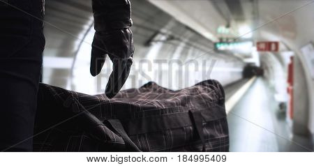 Terrorist and dangerous criminal in subway with suspicious black bomb bag. Bomber in underground metro tunnel. Safety threat in public transport. Terrorism concept.