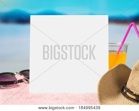 Summer offer background template for promotion and sales. Sunglasses, cocktail and brimmed hat on towel with beautiful paradise view on beach. Empty white paper card with free blank copy space.